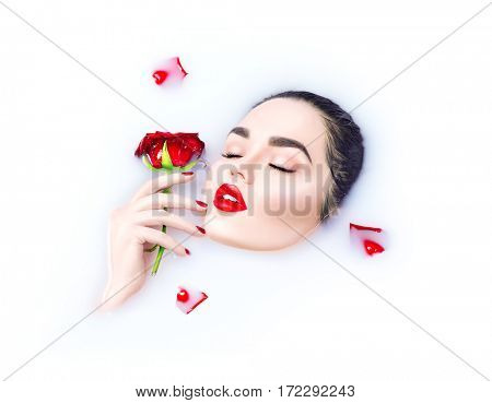 Beauty young woman taking milk bath, spa and skin care concept. Beautiful model girl with bright makeup holding red rose flower in her hand and relaxing in milk bath. Health care concept, Cosmetics