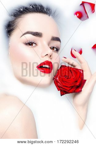 High Fashion model girl taking milk bath, spa and skin care concept. Beauty young Woman with bright makeup and red rose flower relaxing in milk bath.