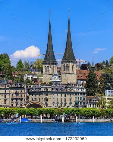 Lucerne, Switzerland - 8 May, 2016: people in boats on Lake Lucerne, towers of the Church of St. Leodegar in the background. The Church of St. Leodegar (German: St. Leodegar im Hof or Hofkirche St. Leodegar) is a landmark of the city  of Lucerne.