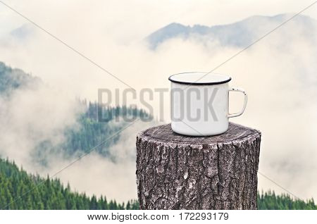 Old mug with a hot drink on a wooden stump in the outdoors on the background of the misty mountains. Photo in vintage color image style. Coffee break outdoors. Morning Still life. Morning at the campsite.