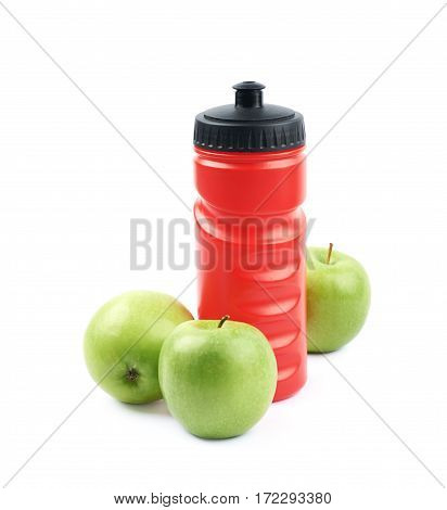 Composition of red plastic drinking bottle next to a pile of green apples, isolated over the white background