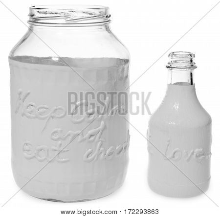 Painted white empty bottle with inscription love and white jar with the inscription Keep calm and eat chocolate. Dish on a white background with slight reflection.