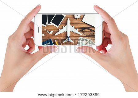 Woman hand using smart phone searching Preparation traveling with pencil money passport airplane watch noted book eyeglasses earphone and photo frame on vintage wooden. Travel concepts.