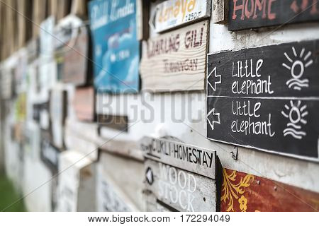 Closeup photo of the wall with many multi-colored signboards. Low aperture photo. Horizontal.