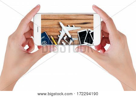 Woman hand using smart phone searching Preparation traveling with airplane Photo frame earphone pencil and passport on vintage wooden background. Travel concepts Isolated on white background.