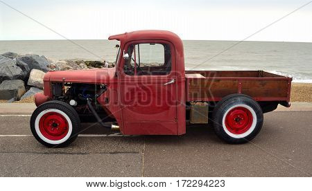 FELIXSTOWE, SUFFOLK, ENGLAND - AUGUST 27, 2016: Classic Hot Rod  pickup truck on seafront promenade with sea in background