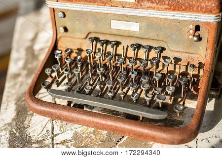 Vintage rusted typewriter on the wooden surface. Closeup low aperture photo. Horizontal.