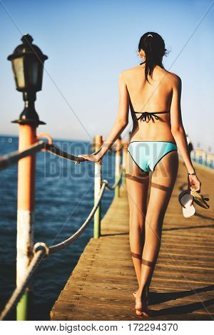 Tinted Image Young Woman Going On A Bridge In The Sea, Back View