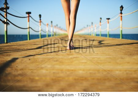 Tinted Image Young Woman's Legs On A Bridge In The Sea