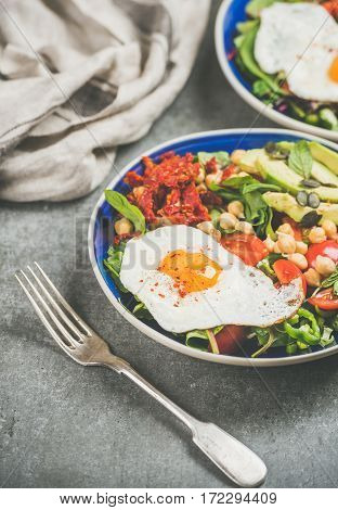 Healthy breakfast with fried egg, chickpea sprouts, seeds, fresh vegetables and greens in bowls over grey concrete background, selective focus. Clean eating, healthy lifestyle, vegetarian food concept