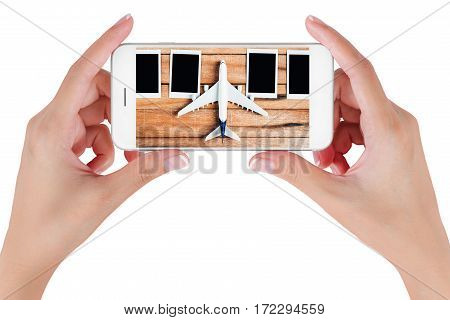 Woman hand using smart phone searching preparation traveling with airplane and photo frame on vintage wooden. Travel concepts Isolated on white background.