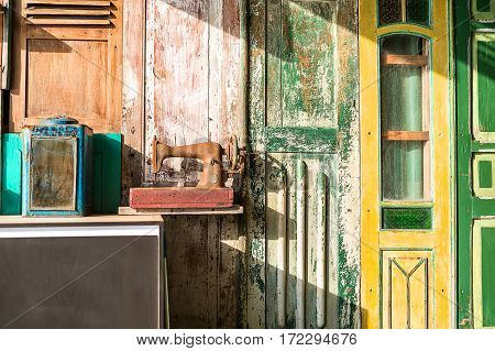 Multi-colored wall decorated with shabby wooden doors. There is a stand with an old box with mirror and a rusted sewing machine. Sunlight shines from the left. Horizontal.