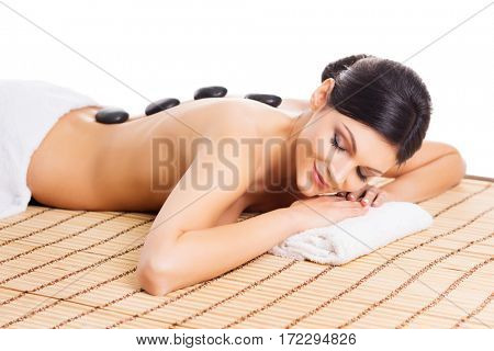 Beautiful, young and healthy woman on bamboo mat in spa salon is having hot stone massage. Isolated on white. Spa, health and healing concept.