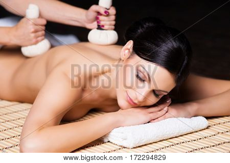 Beautiful, young and healthy woman on bamboo mat in spa salon is having massage. Spa, health and healing concept.