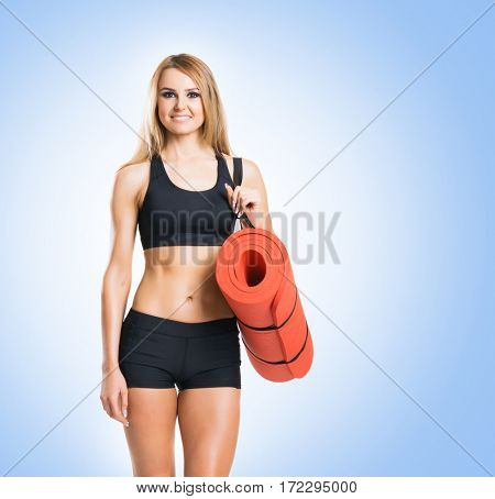 Fit, healthy and sporty woman in sportswear over blue background.