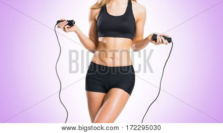 Fit, healthy and sporty woman in sportswear over violet background.