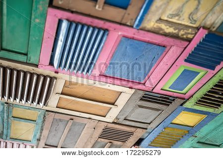 Many colorful wooden panels in the form of the doors. They are pink, blue, yellow, green, brown, beige. Closeup low aperture photo. Horizontal.
