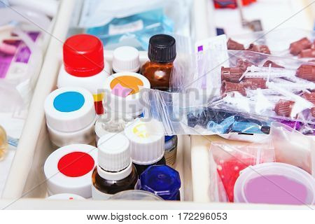 Close up photo of dentist's tools drawer with various small bottles