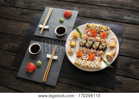 Japanese food restaurant, sushi maki gunkan roll platter. Set for two with chopsticks, ginger, soy, wasabi. Above view on rustic wood background and black slate plates.