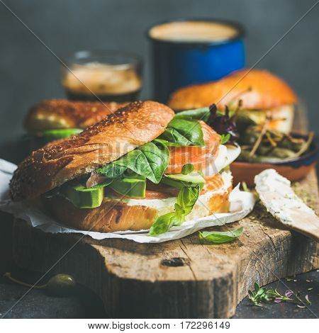 Bagel with salmon, avocado, cream-cheese, basil, espresso coffee, capers on rustic wooden board over dark background, selective focus, square crop. Healthy or diet bkeakfast concept