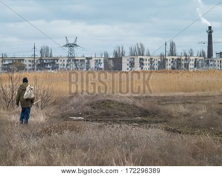 The fisherman with a backpack goes on the field