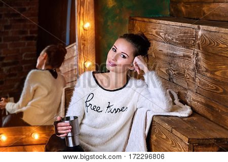 Young brunette holdind a thermocup and sitting in front of mirror with lights
