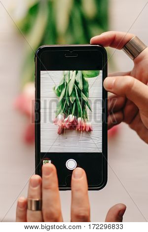 Hand Holding Phone Taking Photo Of Stylish Flower Flat Lay, Pink Tulips On White Wooden Rustic Backg