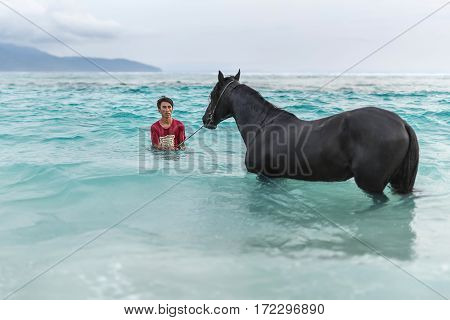 Gili Trawangan, Indonesia - 25 January 2017: man with horse in the sea on the background of the cloudy sky and mountains. Editorial photo. Horizontal.