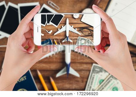 Woman hand using smart phone taking photo for preparation traveling with pencil money passport airplane watch noted book eyeglasses earphone and photo frame on vintage wooden background.