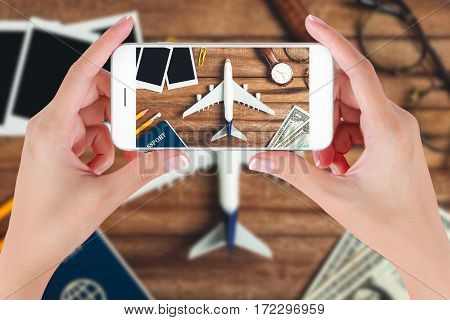 Woman hand using smart phone taking photo for preparation traveling with pencil money passport airplane watch eyeglasses and photo frame on vintage wooden background. Travel concepts.