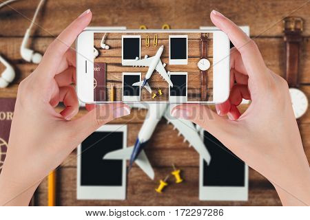 Woman hand using smart phone taking photo for preparation traveling with pencil passport airplane watch blank photographs and earphone on vintage wooden background. Travel concepts.