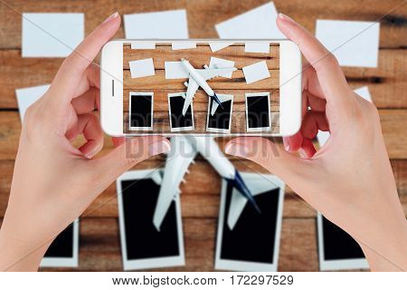 Woman hand using smart phone taking photo for preparation traveling and to do list with paper noted airplane and photo frame on vintage wooden background. Travel concepts blurry background.