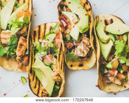 Healthy corn tortillas with grilled chicken fillet, avocado, fresh salsa, limes over light grey marble table background, top view. Healthy food, gluten-free, allergy-friendly, weight loss concept