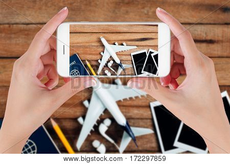 Woman hand using smart phone taking photo for preparation traveling with airplane Photo frame earphone pencil and passport on vintage wooden background. Travel concepts blurry background.