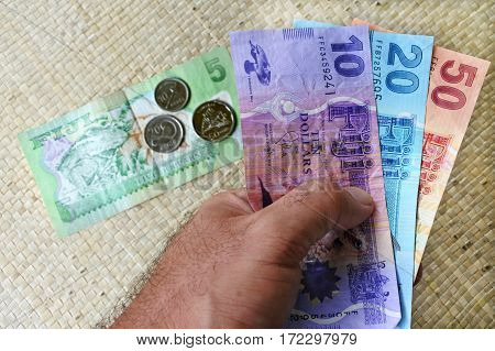 Tourist hand hold a Fijian money currency. Travel concept copy space