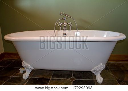 Vintage type footed white bath tub in olive green bathroom with slate tile floor