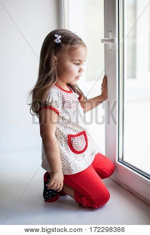 Child girl looking out the window and waiting somebody