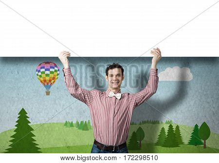 Young funny guy in checked shirt holding blank banner above head