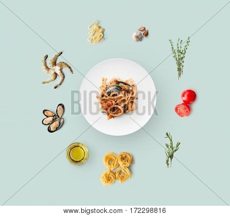 Cooking italian food, seafood pasta, isolated on blue. Frutti di mare with fettuccine spaghetti. Mussels, prawn, shrimp, calamari rings and other ingredients around plate with dish