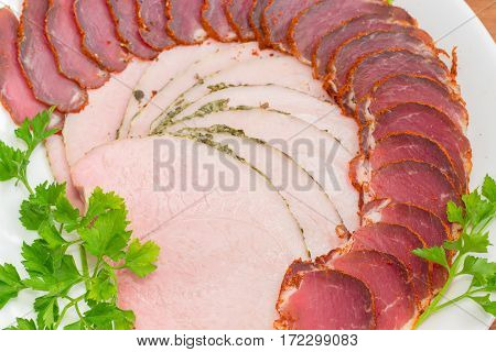 Fragment of white dish with sliced dried pork tenderloin ham and twigs of parsley closeup