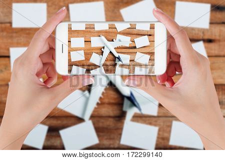 Woman hand using smart phone taking photo for preparation traveling and to do list with paper noted and airplane on vintage wooden background. Travel concepts blurry background.