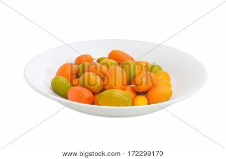 Fresh oval kumquats on a white dish on a light background