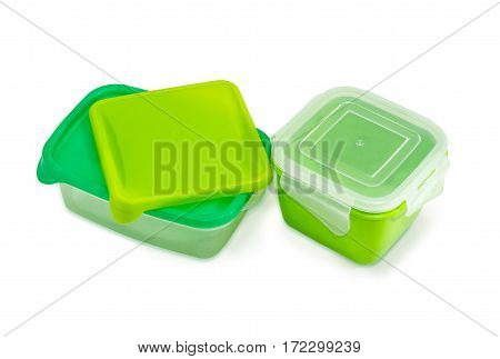 Two different green reusable plastic food storage containers with covers for home use on a light background