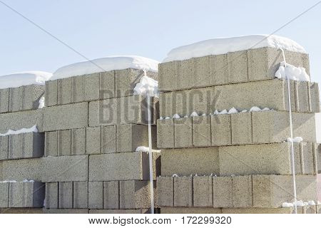 Concrete masonry units packed on pallets and covered snow closeup on an outdoor warehouse in winter sunny day