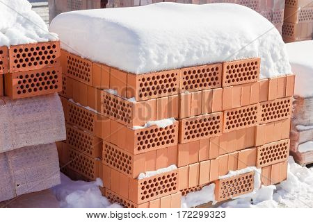 Red perforated bricks with round holes covered snow on a pallet on an outdoor warehouse in winter sunny day