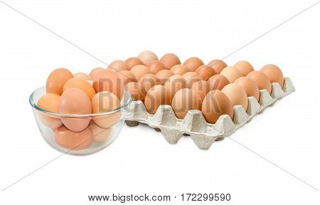 Glass bowl with the brown chicken eggs against the background of the cardboard egg tray of eggs on a light background