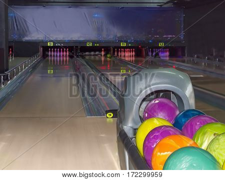 Playing area with several lanes bowling pins and colored bowling balls on the foreground in the modern pin bowling alley