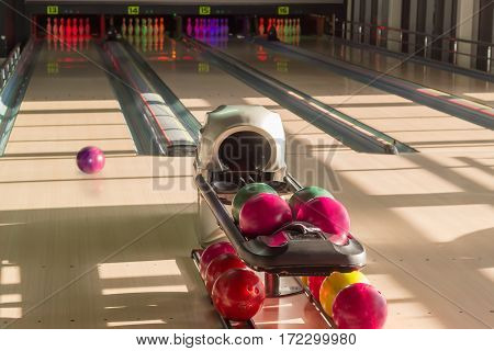 Playing area with several lanes with bowling pins bowling ball rolling along the lane and colored bowling balls on the foreground in the modern pin bowling alley