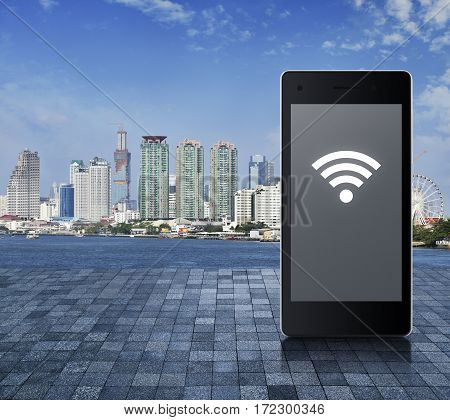 Wi-fi icon on modern smart phone screen on stone tile floor over office city tower river and blue sky Technology and internet concept