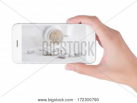 Woman using her smart phone searching medicine information white pills and Blank Medicine bottle pouring on white background. in health care and medicine concept Isolated on white background.